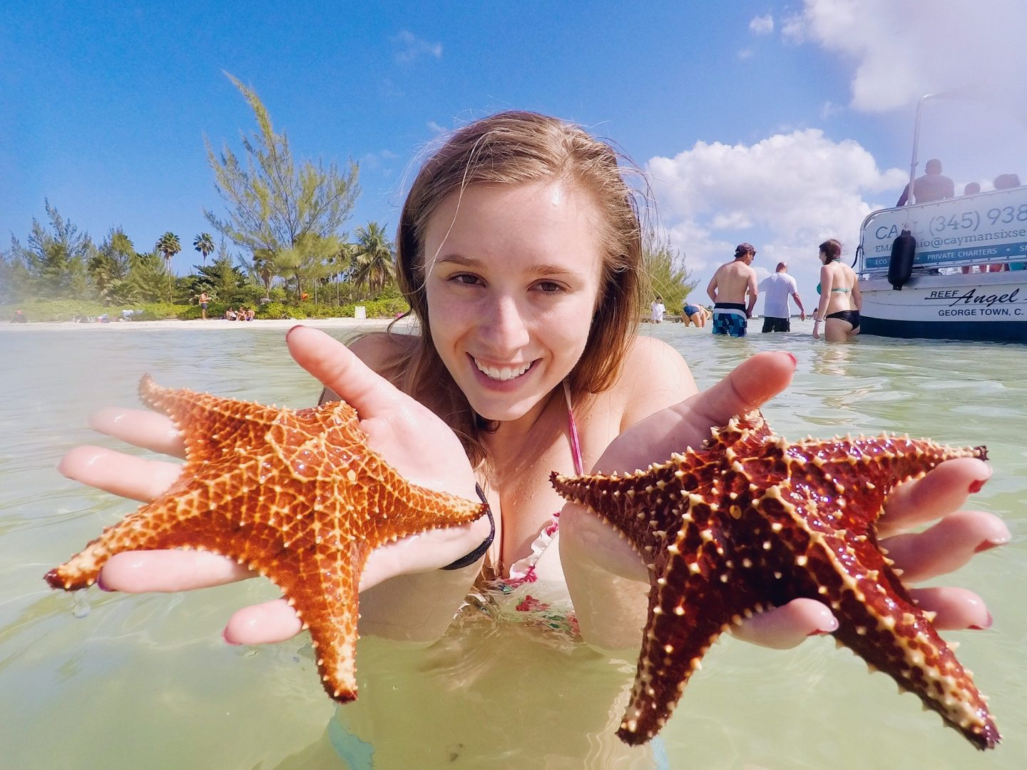 Posing with two starfish at Starfish Point in the Cayman Islands!