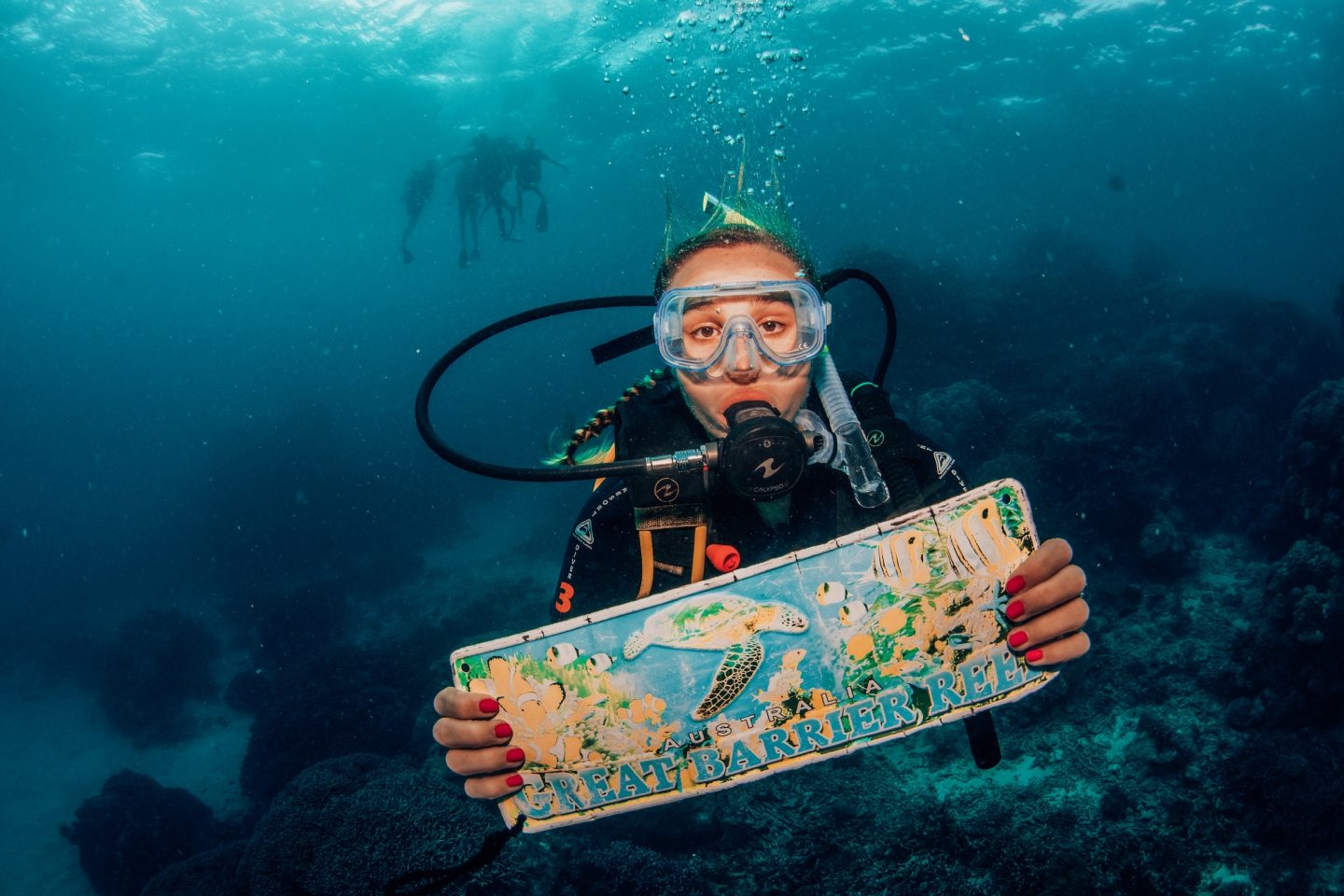 Posing with a Great Barrier Reef sign underwater while scuba diving in the Great Barrier Reef.