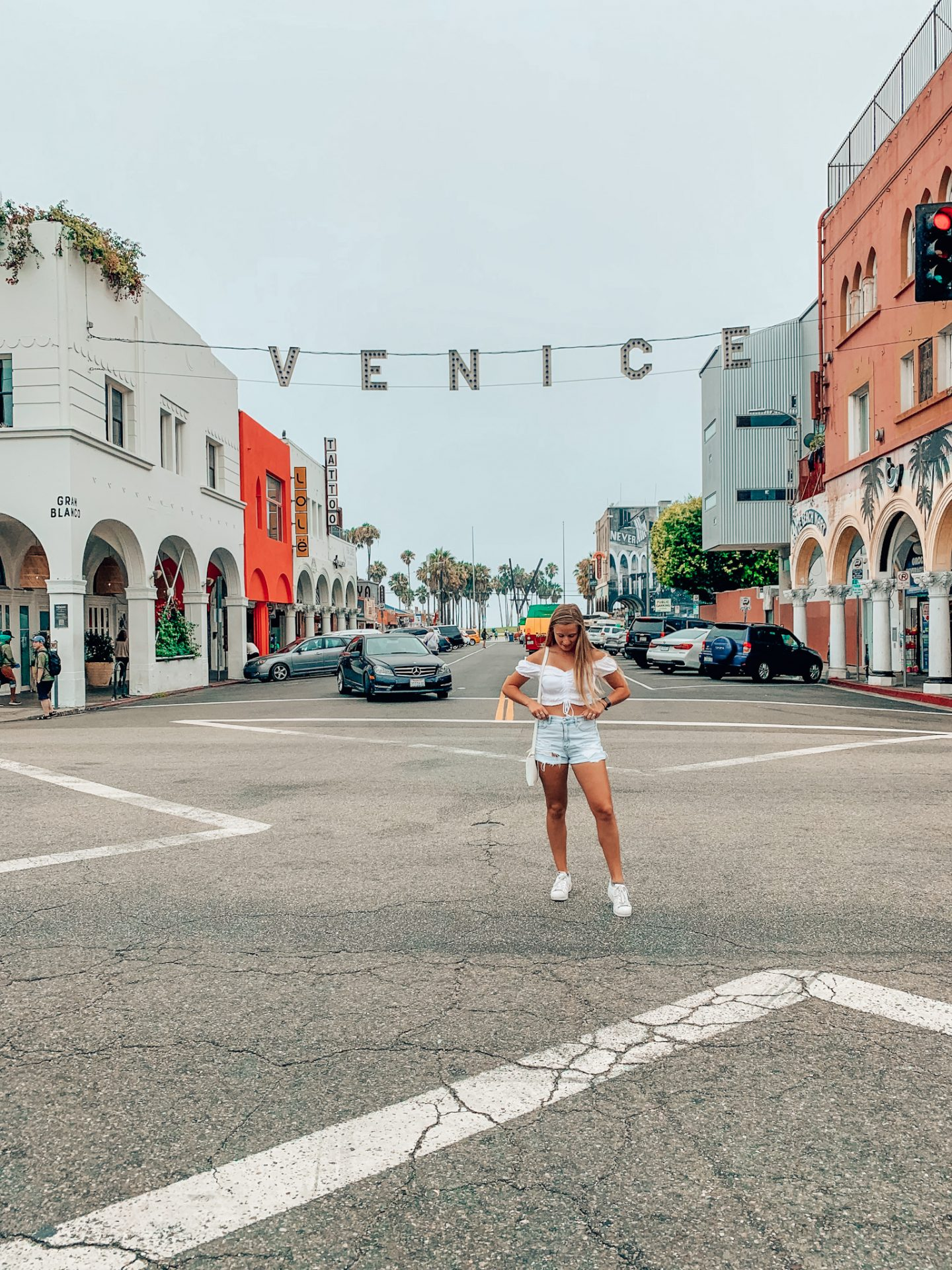 """Posing under the famous """"Venice"""" sign in Venice beach, Los Angeles."""