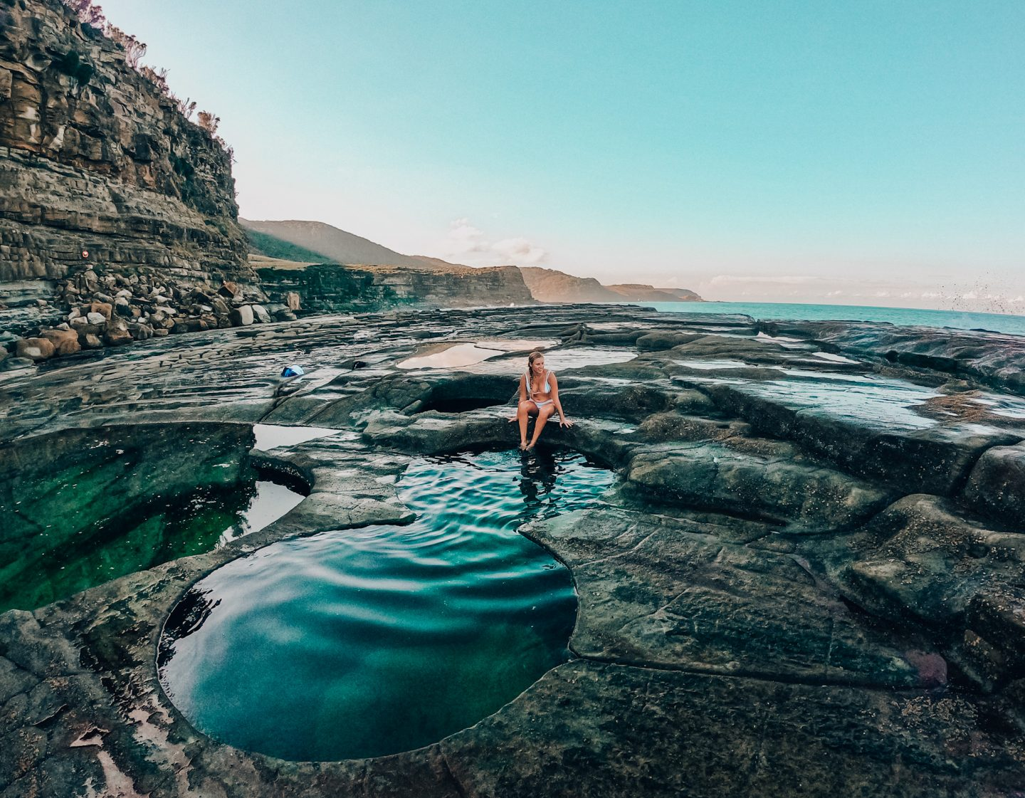 Natural pool shown in rocks with girl sitting on edge with legs in pool in Sydney, Australia park