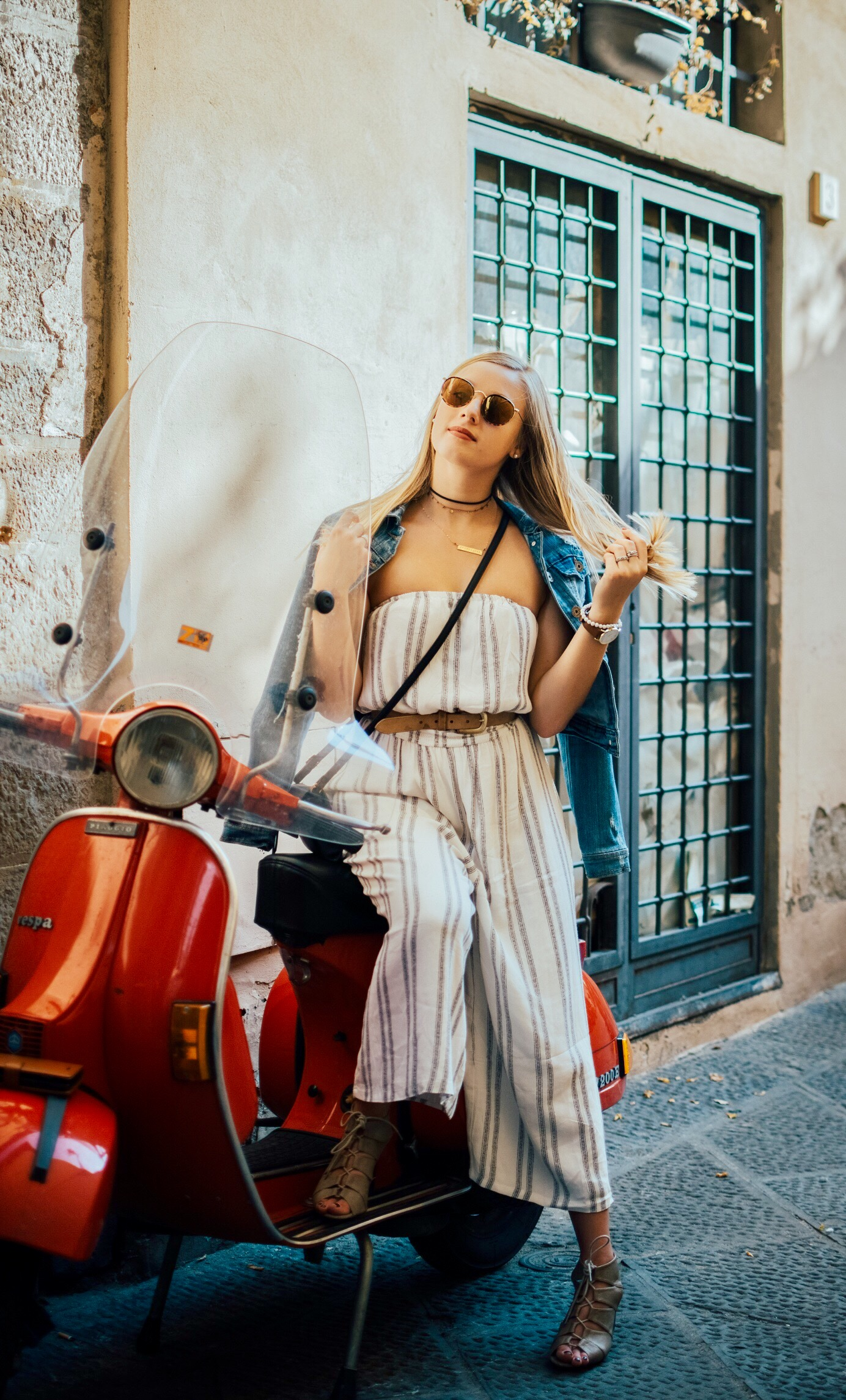 Girl poses on red vespa wearing striped jump suit and jean jacket while studying abroad in Florence, Italy