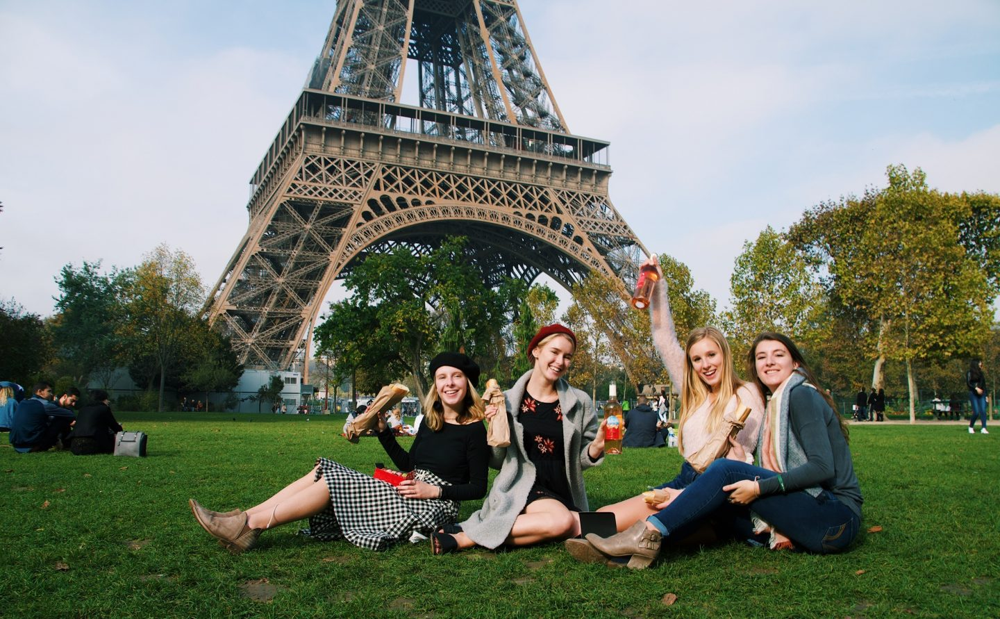 4 girls pose on grass in front of Eiffel Tower in Paris, France with wine and food while studying abroad in Europe