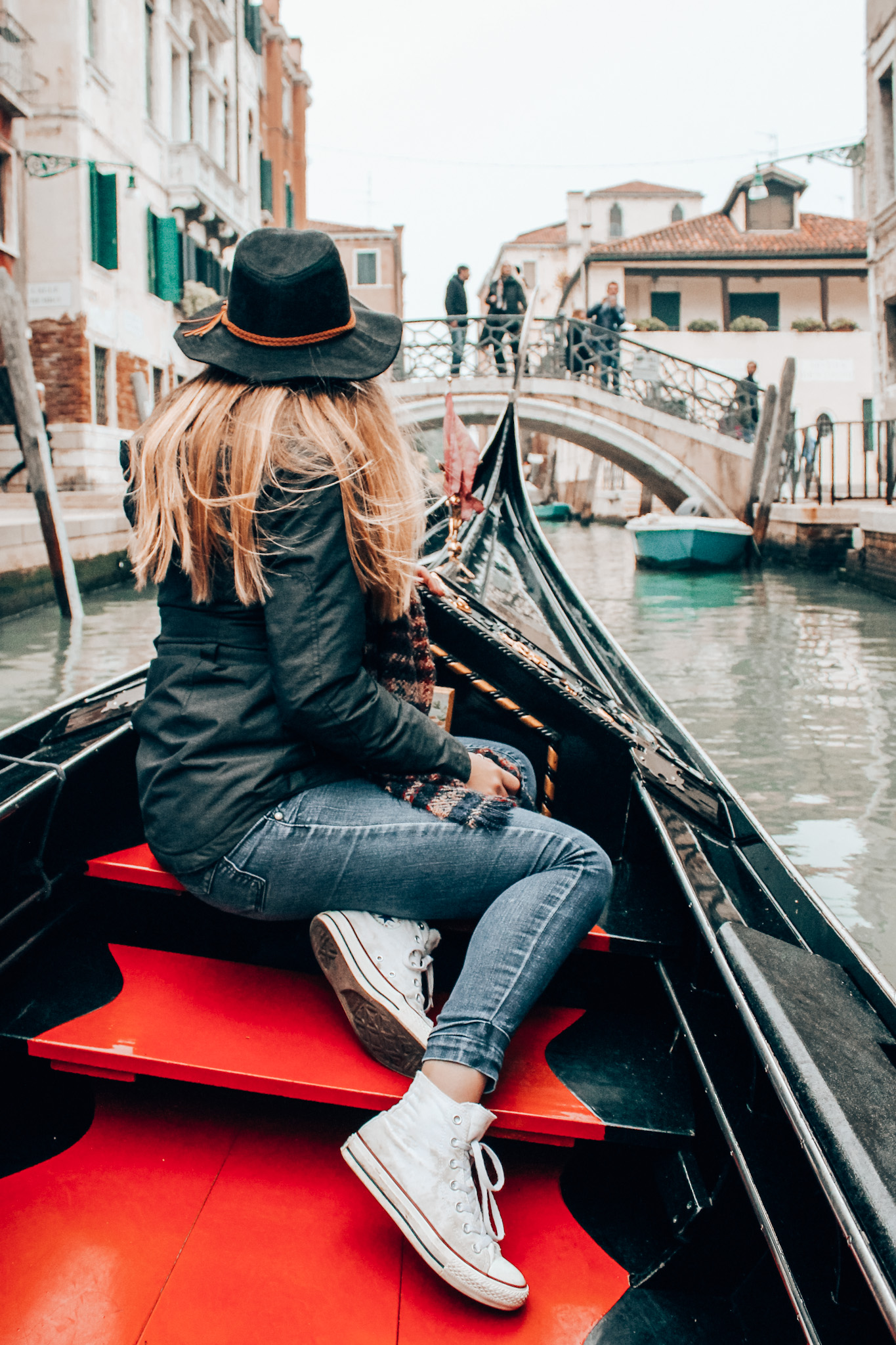 Girl poses on gondola in Venice, Italy wearing a black hat and jacket while studying abroad in Europe