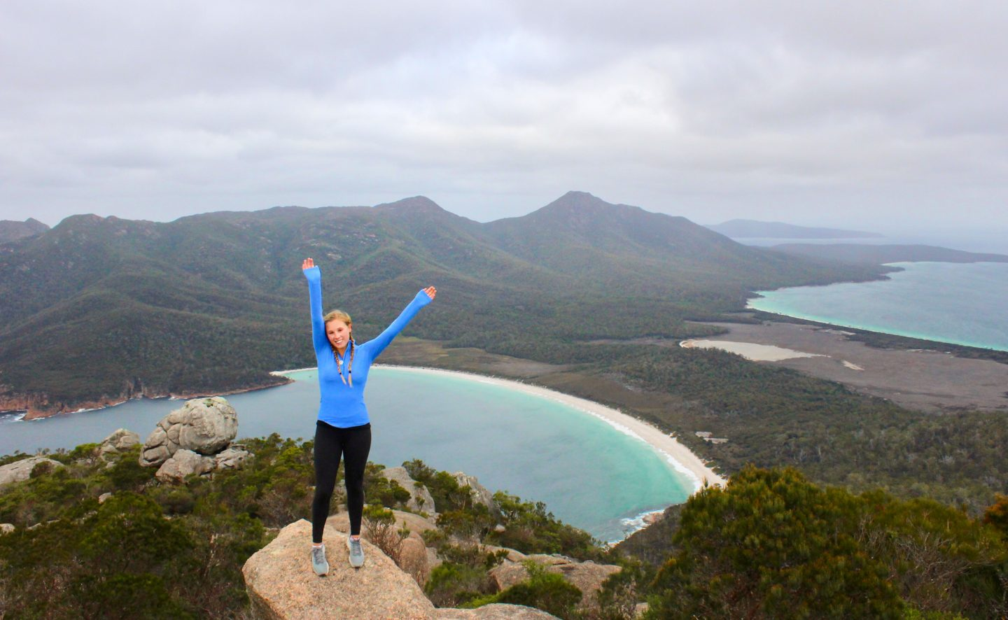Girl poses with her arms up at the top of Mt. Amos in Tasmania, Australia. You can see Wineglass Bay in background
