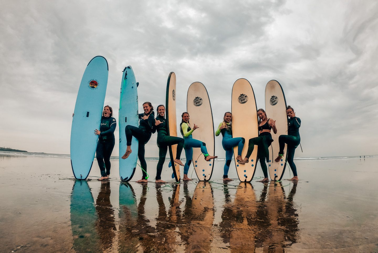Girls pose with surfboards on a beach in Australia