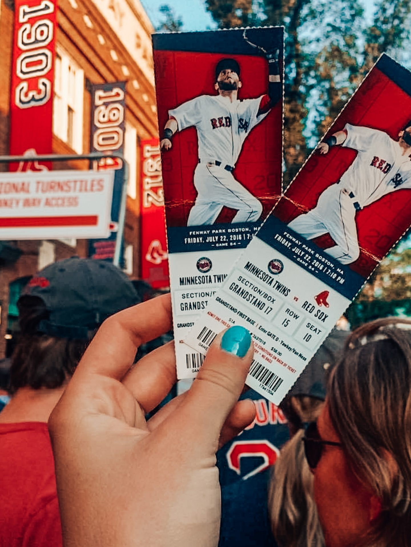 Girl holds up two baseball tickets in front of Fenway Park in Boston, MA