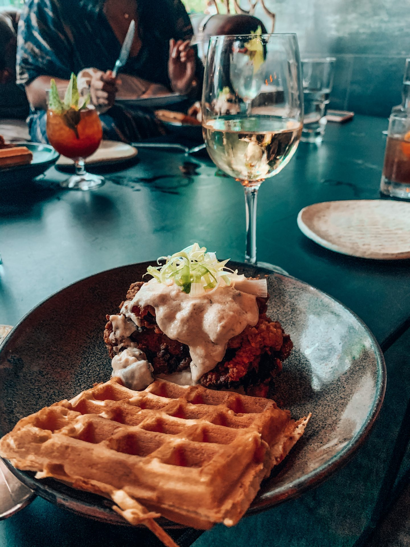 Shot of waffles and chicken on plate with glass of white wine on table at Committee in Boston