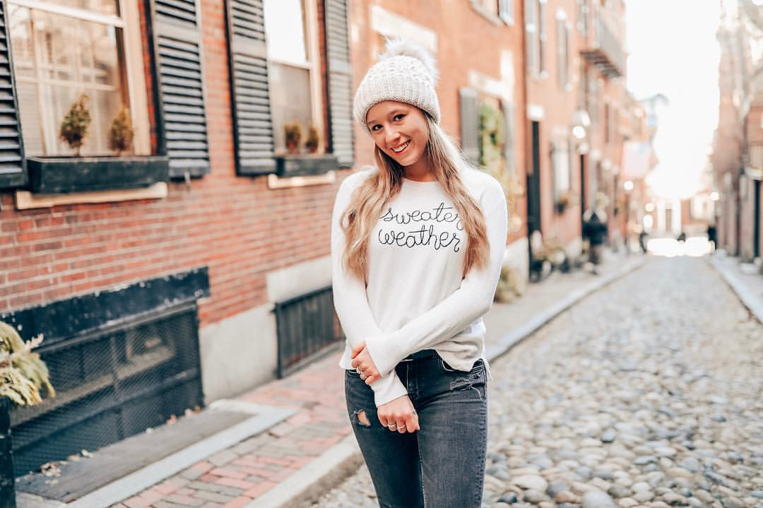 Girl poses with hat on in street in Beacon Hill neighborhood during a weekend in boston