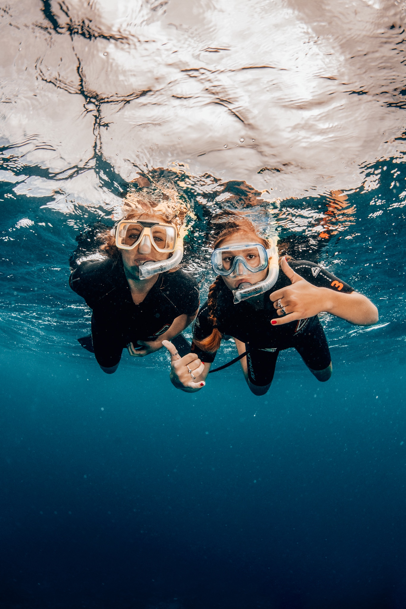 Two girls pose underwater with snorkel gear in the Great Barrier Reef in Australia